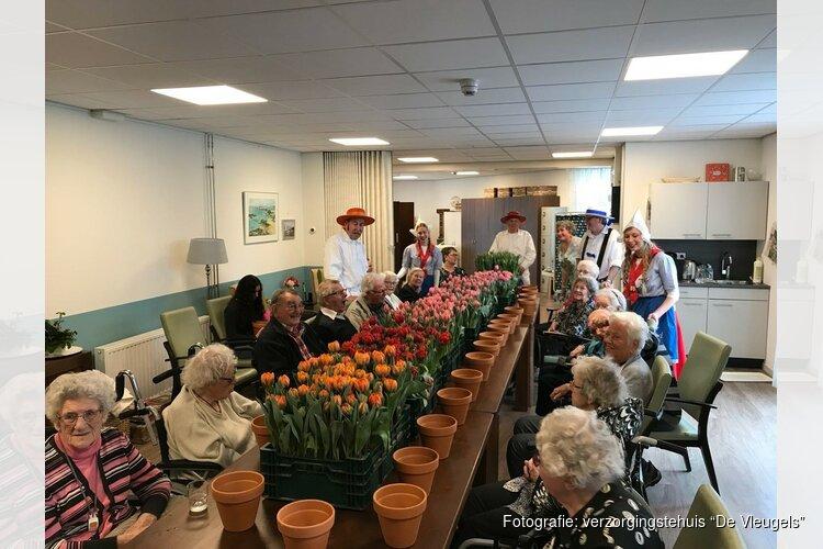 Kaasdragers delen tulpen uit in verzorgingstehuis 'De Vleugels'